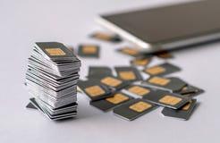Las tarjetas de Gray SIM se recogen en una pila al lado del dispersado otras tarjetas de SIM Fotografía de archivo libre de regalías