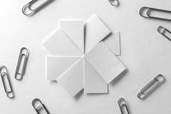 Las tarjetas de visita en blanco avivan los clips dispersados woth de la pila en el tex blanco Fotos de archivo
