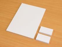 Las tarjetas de visita esconden la maqueta con una pila de papeles Imágenes de archivo libres de regalías