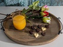 Las tarjetas del día de San Valentín excelentes desayunan del zumo de naranja, de los chocolates del corazón y de las rosas imagen de archivo