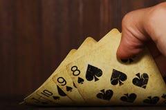 Las tarjetas del póker del vintage holded en una mano del hombre fotos de archivo libres de regalías