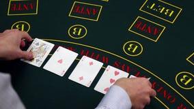 Las tarjetas del trato del crupié en la tabla verde en el casino, se llevan metrajes