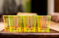 Las tazas amarillas para los cócteles se alinearon uno al lado del otro en una superficie de madera Imagen de archivo libre de regalías