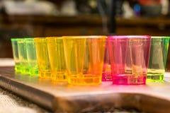 Las tazas amarillas, rojas, verdes para los cócteles se alinearon uno al lado del otro en una superficie de madera Fotos de archivo libres de regalías