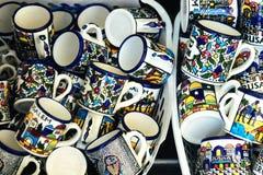 Las tazas azules, brillantes, coloridas de mucho recuerdo en regalo y el presente hacen compras foto de archivo
