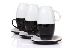 Las tazas blancas invertidas se colocan en las tazas negras con las placas de la pila Fotografía de archivo