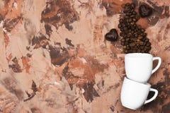 Las tazas blancas para el café express llenaron de los granos de café y del chocolate i Foto de archivo libre de regalías