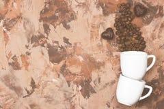 Las tazas blancas para el café express llenaron de los granos de café y del chocolate i Imagenes de archivo