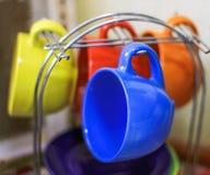 las tazas coloreadas brillantes en una ayuda metal platos en casa foto de archivo libre de regalías