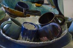 Las tazas coloreadas de cerámica mienten en una situación de la placa en la tabla imagen de archivo
