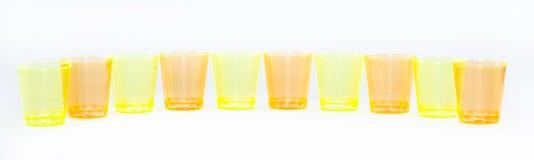 Las tazas coloreadas se alinearon uno al lado del otro en un fondo blanco - amarillo y naranja Imágenes de archivo libres de regalías