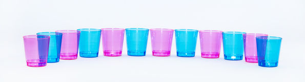 Las tazas coloreadas se alinearon uno al lado del otro en un fondo blanco - rosa y azul Fotos de archivo