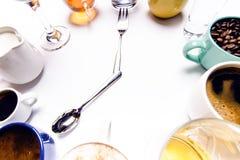 Las tazas con los líquidos les gusta un café, leche, vino, alcohol, jugo apilado en un círculo El reloj consiste en doce tazas Ti Fotos de archivo libres de regalías