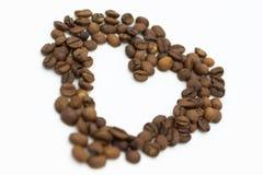 Las tazas de café arreglaron en un arreglo en forma de corazón en los vagos blancos Imagenes de archivo