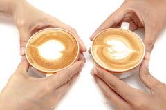 Las tazas de café de corazón del arte del latte forman, bebiendo juntas, en el fondo blanco aislado Fotos de archivo libres de regalías