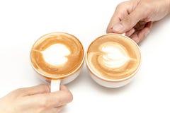 Las tazas de café de corazón del arte del latte forman, bebiendo juntas, en el fondo blanco aislado Fotos de archivo