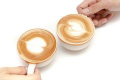 Las tazas de café de corazón del arte del latte forman, bebiendo juntas, en el fondo blanco aislado Foto de archivo libre de regalías