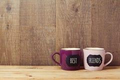Las tazas de café en la tabla de madera con la muestra de la pizarra y los mejores amigos mandan un SMS Celebración del día de la fotografía de archivo libre de regalías