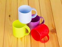 Las tazas multicoloras plásticas en un fondo encienden la madera fotografía de archivo