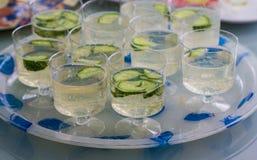 Las tazas plásticas refrescadas restauran del agua y de los pepinos Imagen de archivo libre de regalías