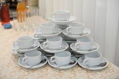 Las tazas y los platillos blancos con las cucharas están en uno a en la forma de una pirámide Foto de archivo