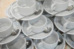 Las tazas y los platillos blancos con las cucharas están en uno a en la forma de una pirámide Imagen de archivo libre de regalías