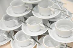 Las tazas y los platillos blancos con las cucharas están en uno a en la forma de una pirámide Fotos de archivo