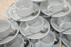 Las tazas y los platillos blancos con las cucharas están en uno a en la forma de una pirámide Imagen de archivo