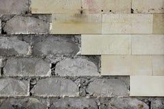 Las tejas beige grandes de la pared se cayeron, la textura de la fundación concreta Trabajo defectuoso foto de archivo