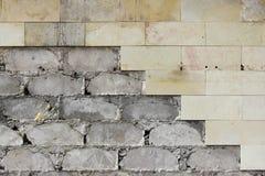 Las tejas beige grandes de la pared se cayeron, la textura de la fundación concreta Trabajo defectuoso imagenes de archivo