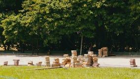 Las tejas multicoloras de la acera en parque del ` s de los niños mienten en la tierra lista para poner almacen de metraje de vídeo