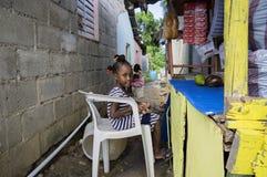 LAS TERRENAS, DOMINIKANSKA REPUBLIKEN - SEPTEMBER 26, 2016: oidentifierat liten flickasammanträde med en docka, i stol och att sä Arkivbild