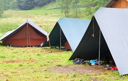 Las tiendas de campaña en un explorador acampan en el césped en las montañas Fotos de archivo