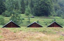 Las tiendas de campaña en un explorador acampan en el césped en las montañas Foto de archivo libre de regalías