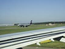Las tierras del avión en la pista Imagen de archivo libre de regalías