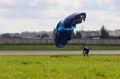 Las tierras del paracaidista en un paracaídas multicolor Fotografía de archivo