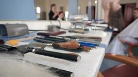 Las tijeras de la peluquería y los accesorios del peluquero en la peluquería, peluquero hacen un peinado en fondo almacen de video