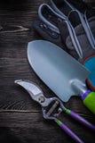 Las tijeras de podar de los guantes de la seguridad dan la espada en el tablero de madera Imágenes de archivo libres de regalías