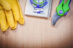 Las tijeras de podar de los guantes protectores que cultivan un huerto cultivan un huerto libreta del alambre del lazo encendido Fotografía de archivo