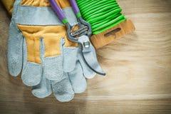 Las tijeras de podar que cultivan un huerto cultivan un huerto los guantes de la seguridad del alambre del lazo en verraco de mad Fotos de archivo libres de regalías
