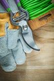 Las tijeras de podar que cultivan un huerto cultivan un huerto los guantes protectores del alambre del lazo en de madera Fotografía de archivo libre de regalías