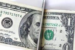 Las tijeras del concepto cortaron los cientos dólares y un billete de dólar en el fondo blanco fotos de archivo