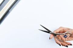Las tijeras del pelo en aislante de las manos en fondo Fotos de archivo libres de regalías
