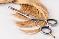 Las tijeras del peluquero con el filamento del pelo rubio en el fondo blanco Foto de archivo libre de regalías
