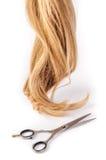 Las tijeras del peluquero con el filamento del pelo rubio en el fondo blanco Foto de archivo