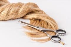 Las tijeras del peluquero con el filamento del pelo rubio en el fondo blanco Fotografía de archivo libre de regalías