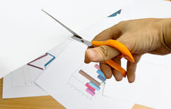 Las tijeras en pleno acto del papel para representan gráficamente y trazan para el trabajo del informe Fotografía de archivo