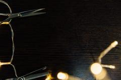 Las tijeras profesionales del estilista del peluquero y una guirnalda mienten en una tabla de madera negra Fotos de archivo libres de regalías
