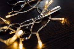 Las tijeras profesionales del estilista del peluquero y una guirnalda mienten en una tabla de madera negra Fotografía de archivo
