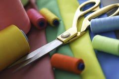 Las tijeras roscan mentira de costura de la tela en negocio de la tabla imagenes de archivo